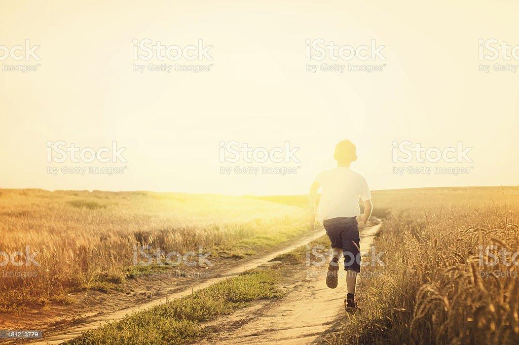 Little boy running on a sunny path. stock photo