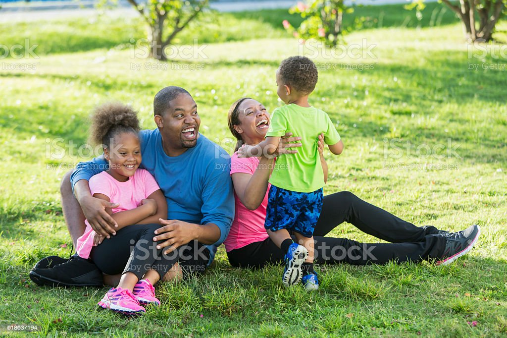 Little boy running to family sitting on ground in park stock photo