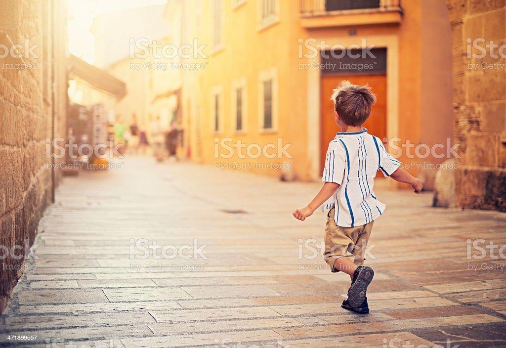 Little boy running up a  mediterranean street stock photo