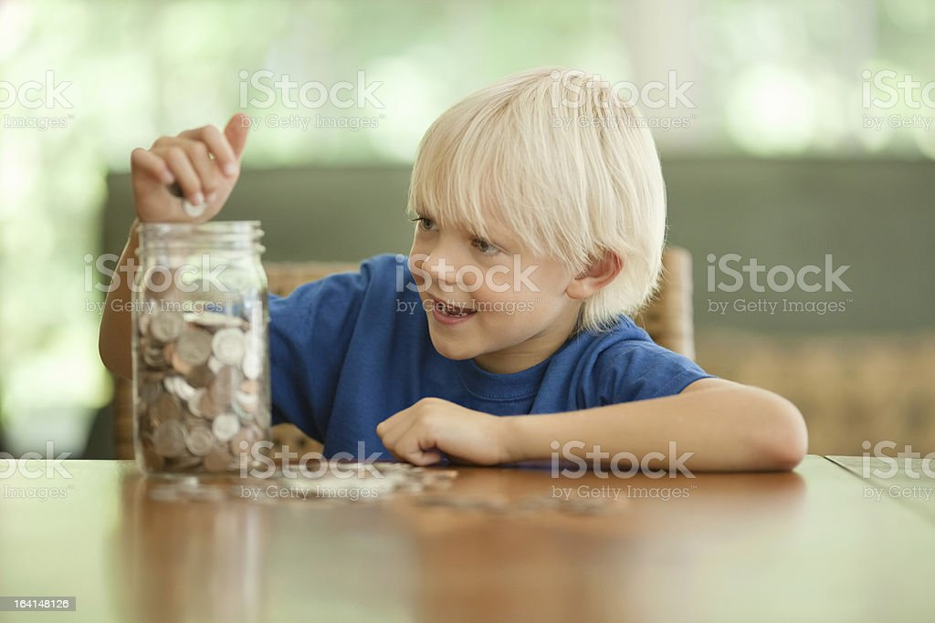 Little Boy Saving Coins In A Glass Jar stock photo