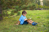 Little boy schoolboy in a park at sunset with a book