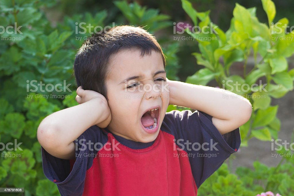 Little boy screaming and covering ears stock photo