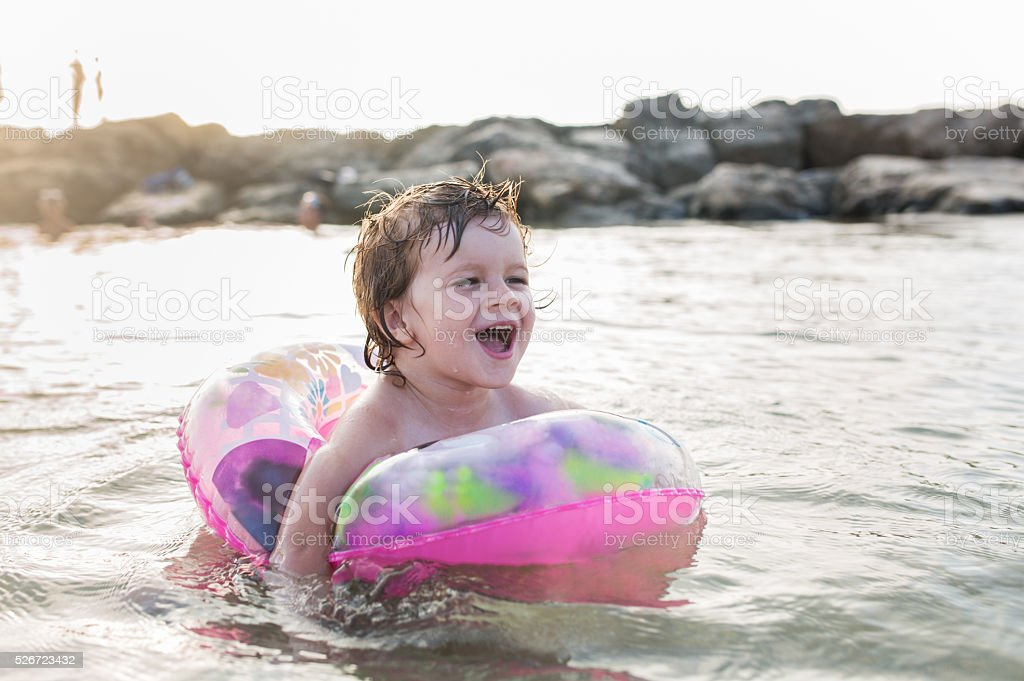 Little boy screaming while being in inflatable ring at sea. stock photo