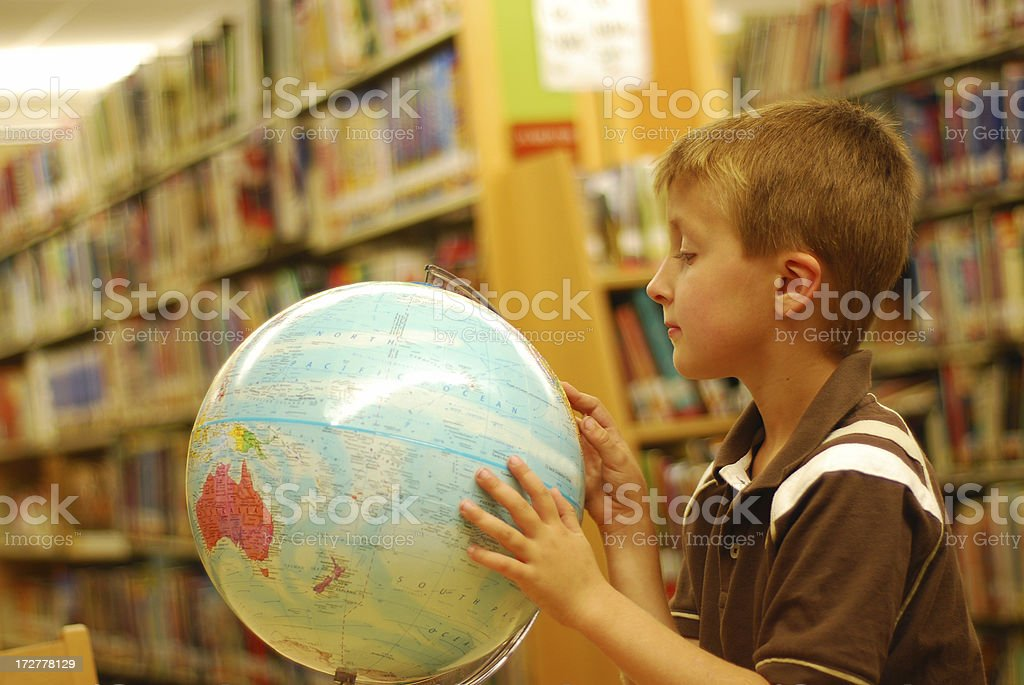 Little boy searching the globe in library royalty-free stock photo