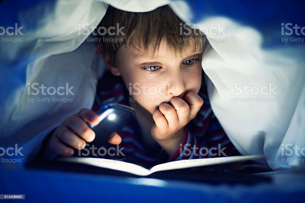 Little boy secretly reading book under sheets stock photo