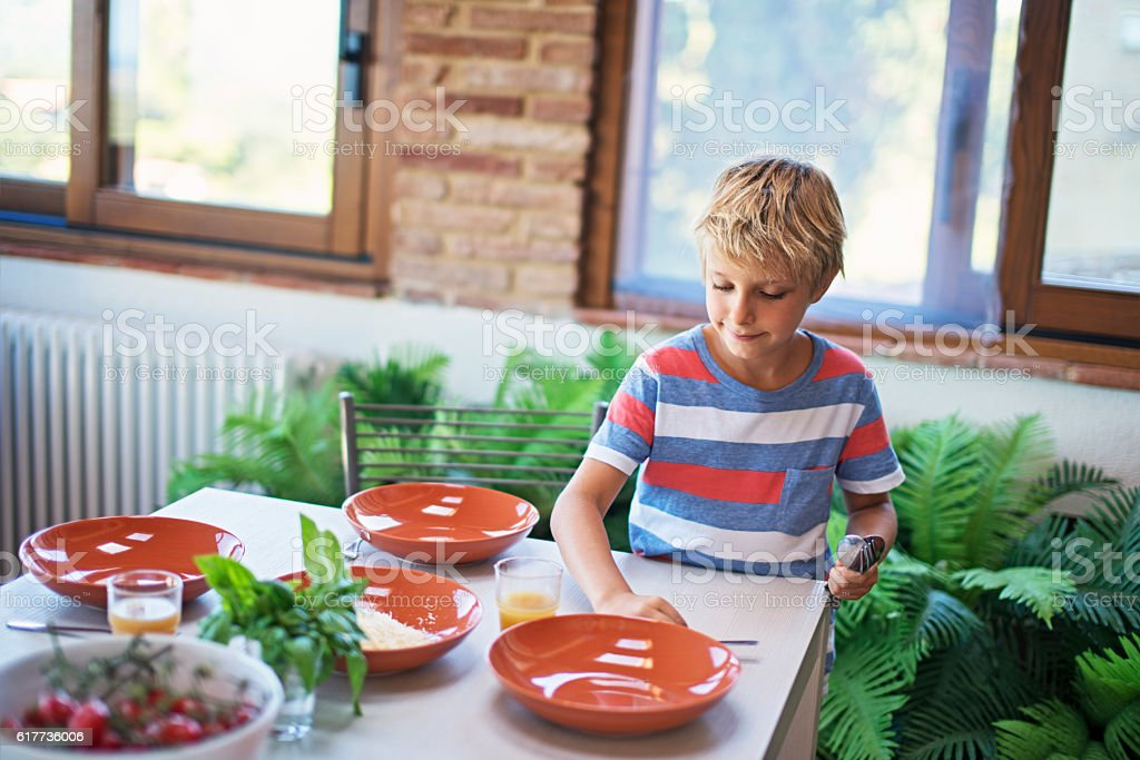 Little boy setting up table for family lunch. stock photo