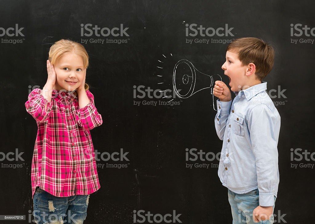 little boy shouting in drawn mouthpiece and girl covering ears stock photo