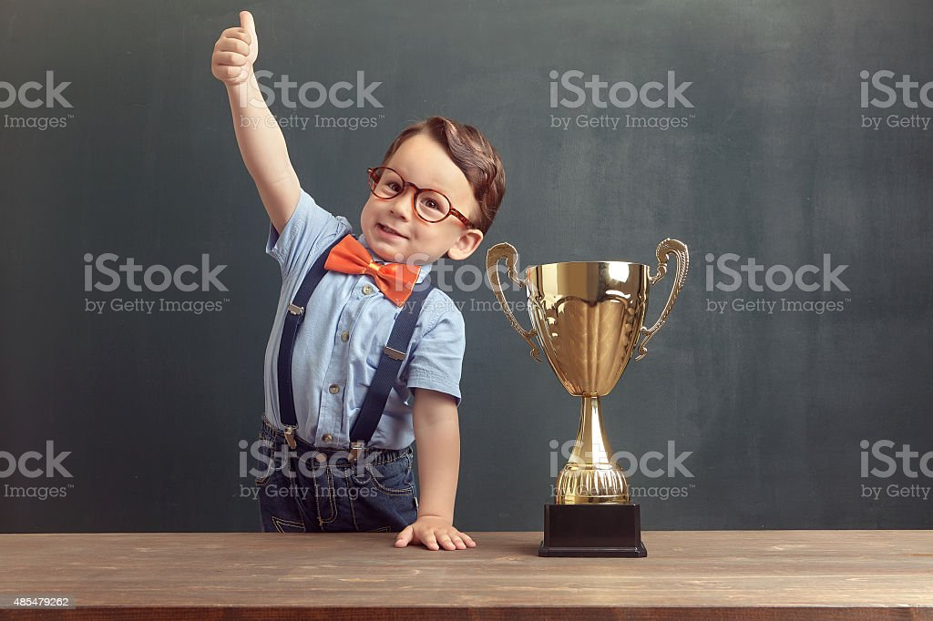 Little boy showing his thumb up with a golden trophy stock photo