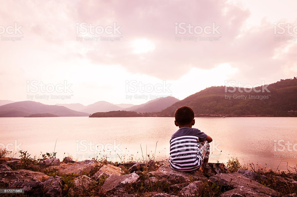 little boy sitting alone at dam in the evening stock photo
