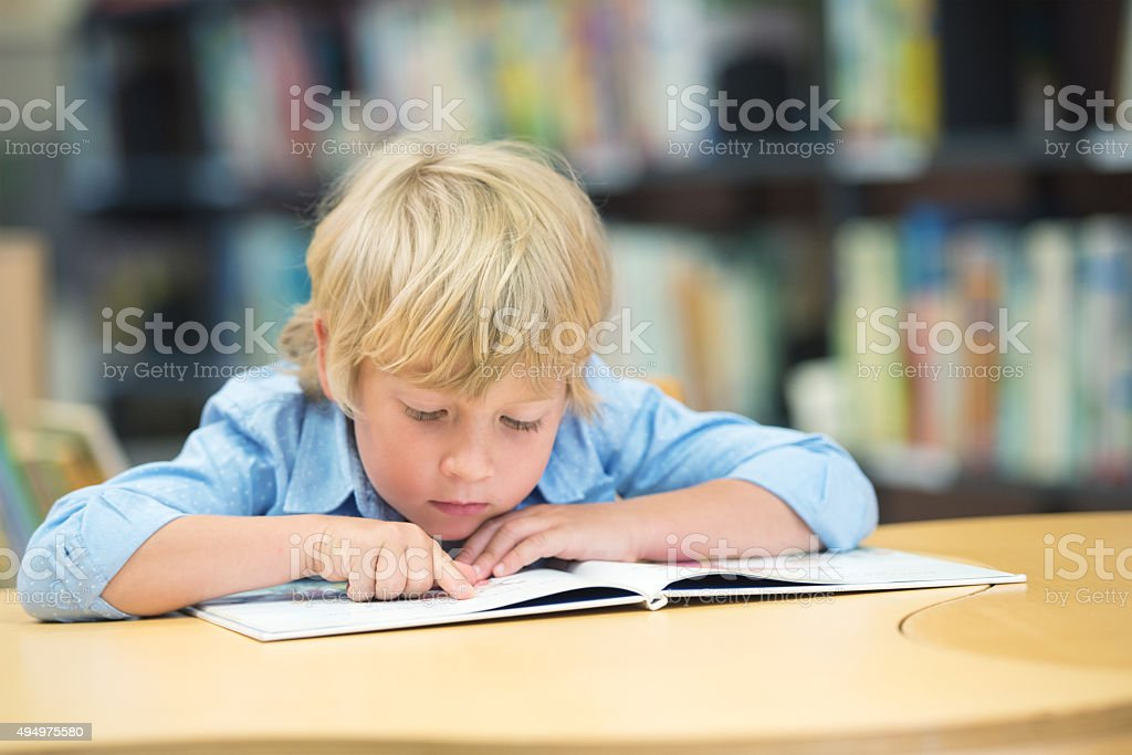 Little boy  sitting at table and reading stock photo