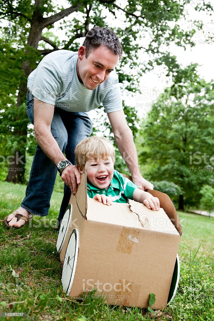 Little boy sitting in a cardboard car and being pushed royalty-free stock photo