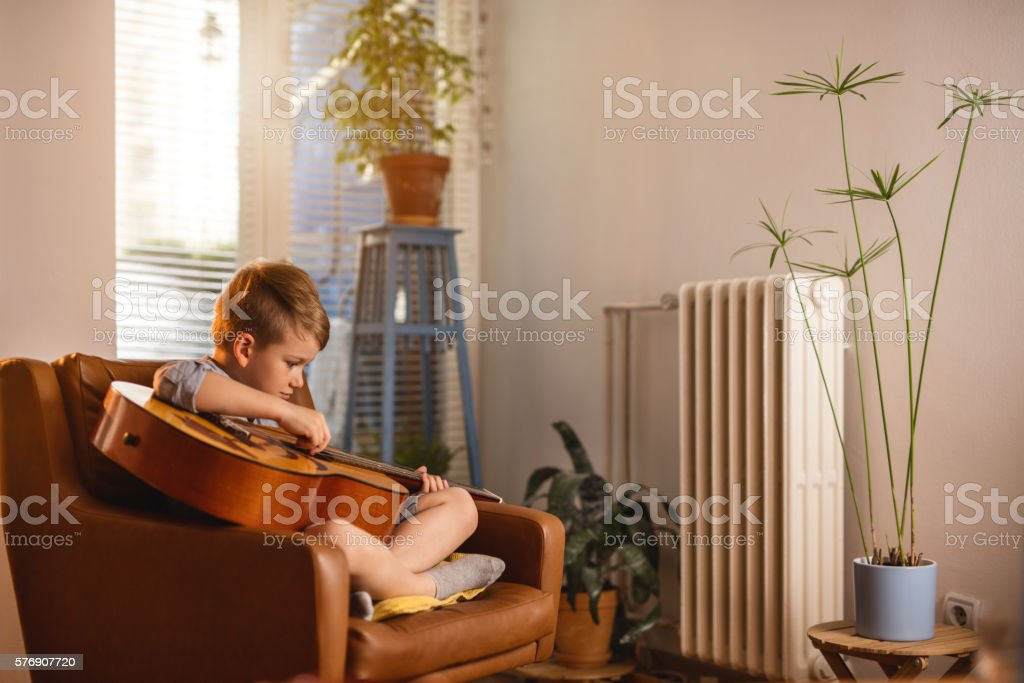 Little boy sitting in armchair and playing acoustic guitar. stock photo