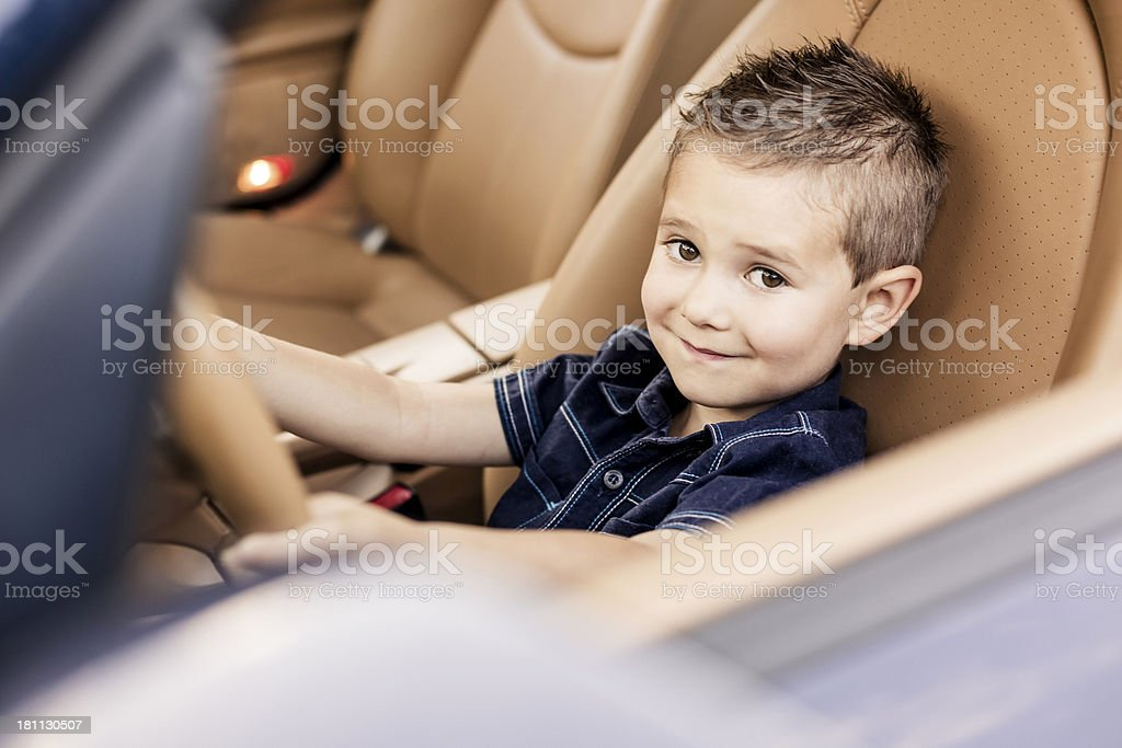 Little Boy Sitting in Driver's Seat of Car royalty-free stock photo