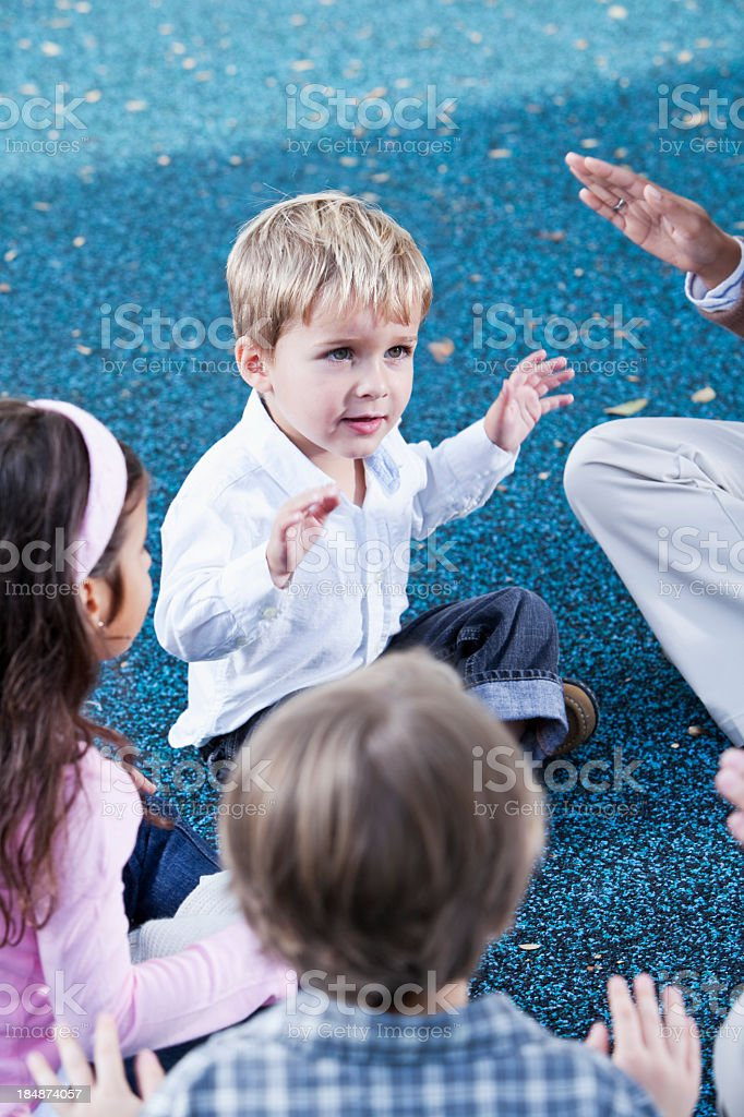 Little boy sitting in group playing patty cake stock photo