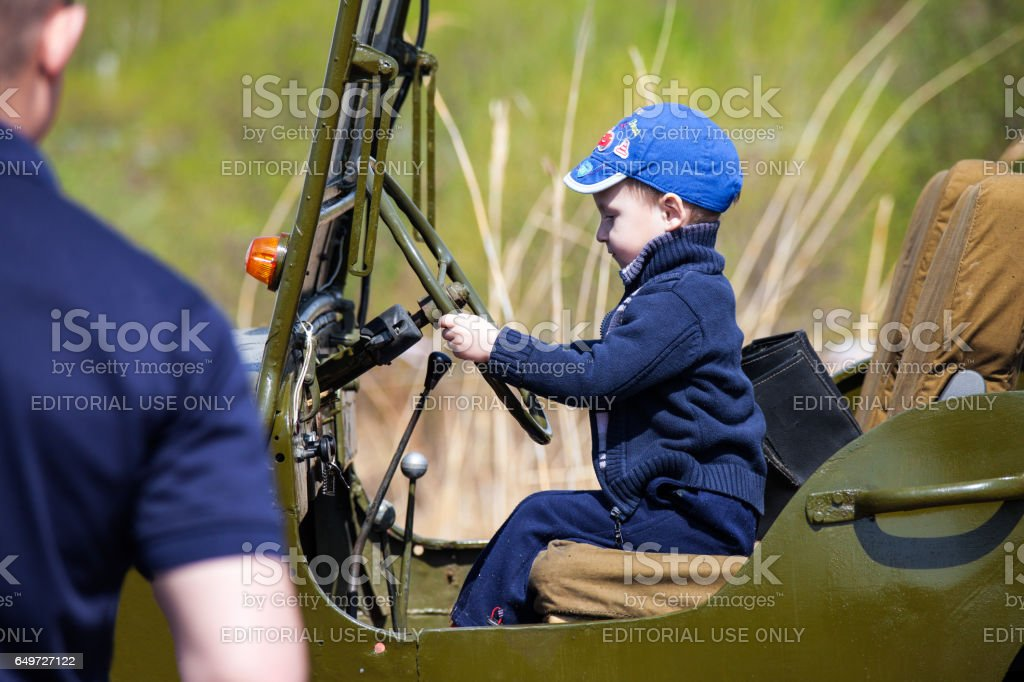 KHABAROVSK, RUSSIA - MAY 14, 2016: Little boy sitting in old Willys MB stock photo