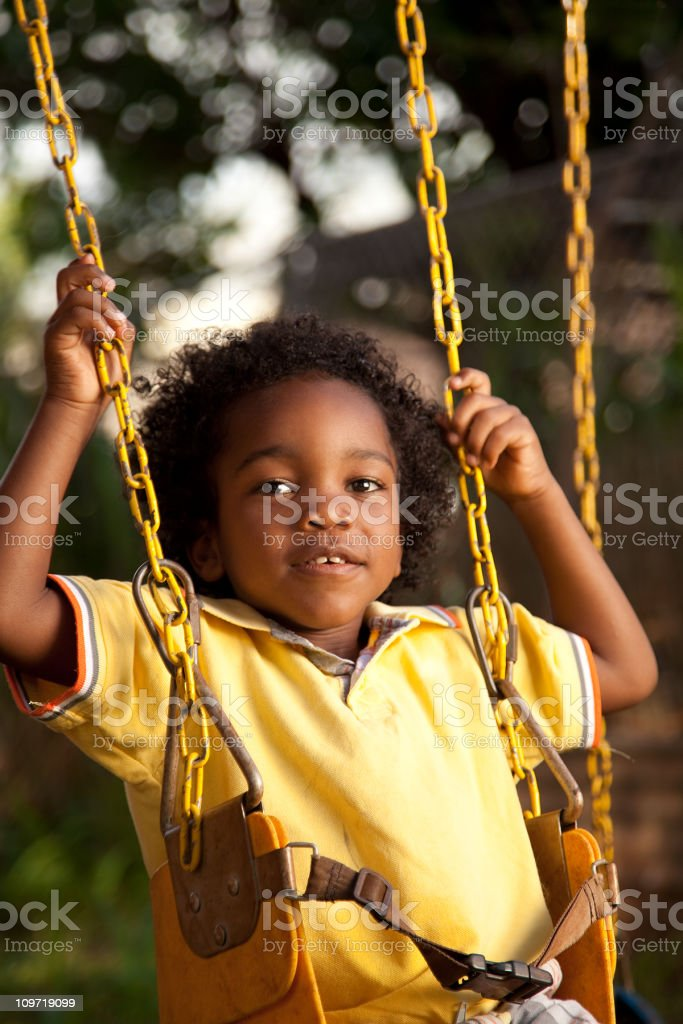 Little Boy Sitting in Playground Swing royalty-free stock photo
