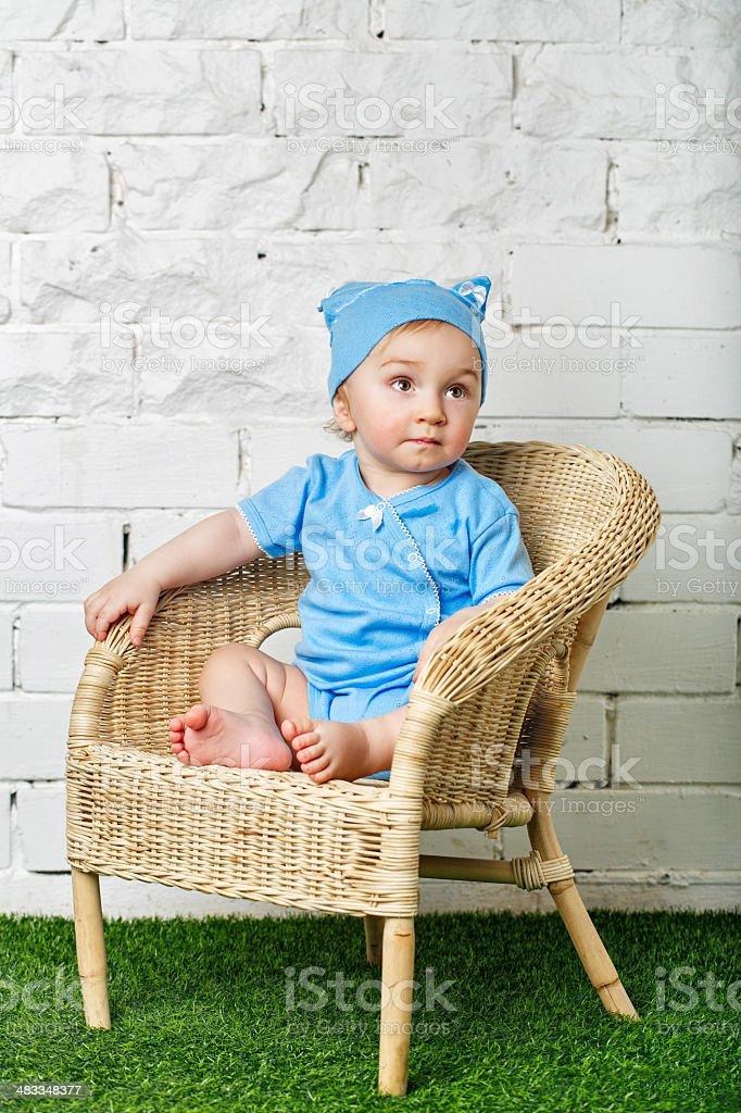 Little boy sitting in wicker chair stock photo