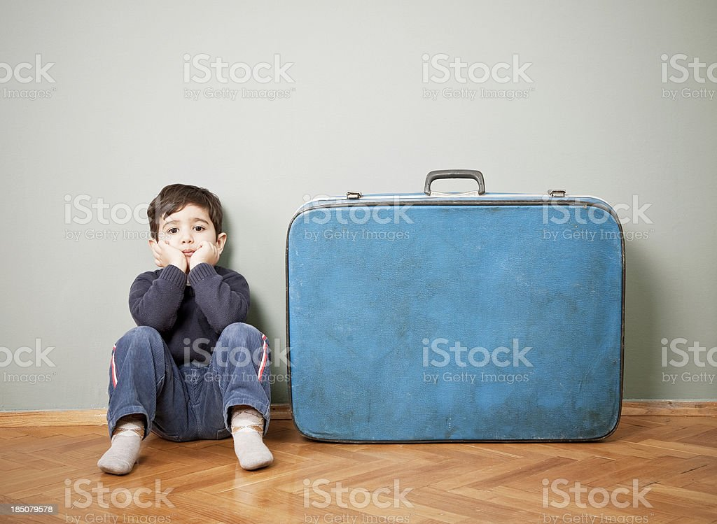 Little boy sitting next to an old suitcase royalty-free stock photo