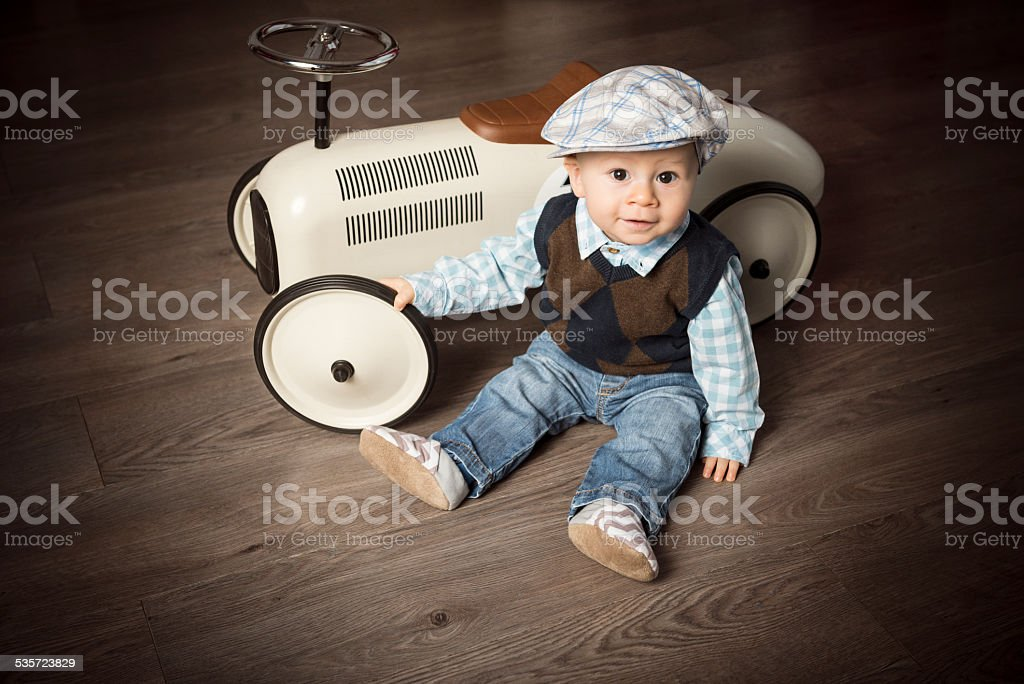 Little boy sitting next to big vintage toy car, indoors stock photo
