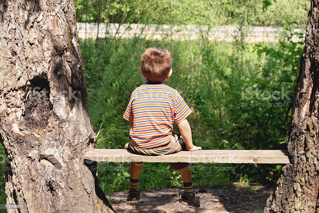 Little boy sitting on a bench and looking at greenery royalty-free stock photo