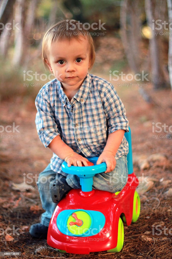 Little boy sitting on a toy car in the park stock photo