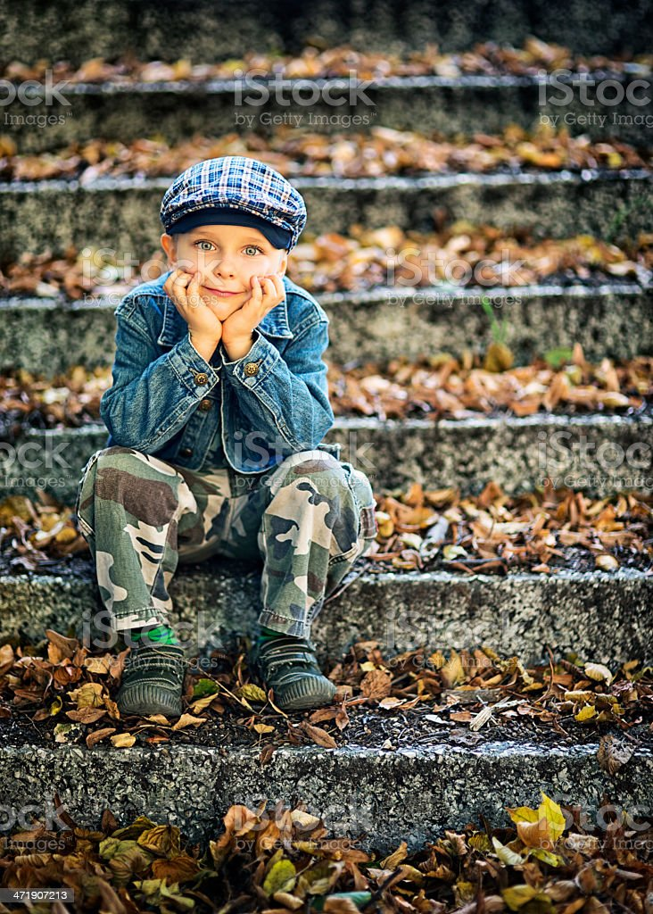 Little boy sitting on autumn stairs royalty-free stock photo
