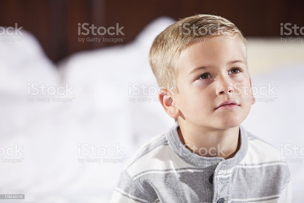 Little boy sitting on bed looking up stock photo