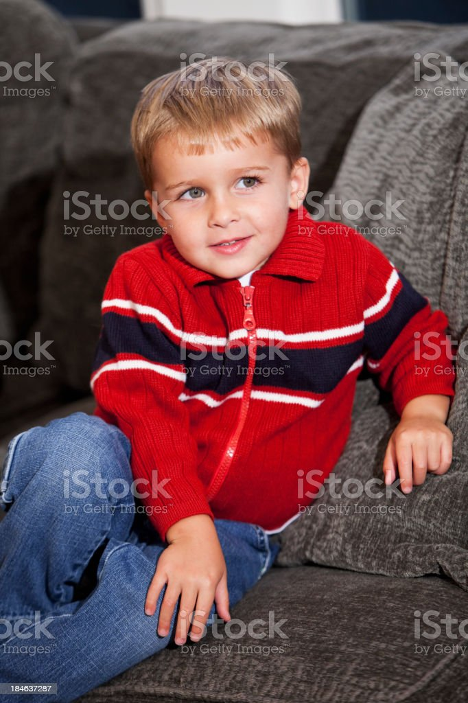 Little boy sitting on couch stock photo