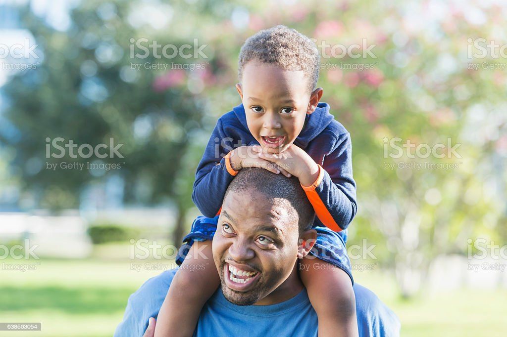 Little boy sitting on father's shoulders stock photo