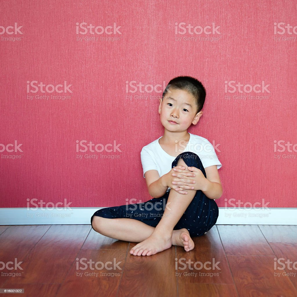Little boy sitting on floor against wall stock photo