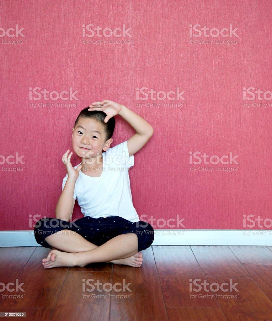 Little boy sitting on floor against wall stock photo