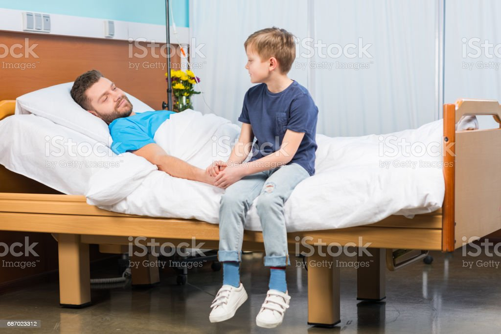 Little boy sitting on hospital bed and looking at sick father, dad and son in hospital stock photo