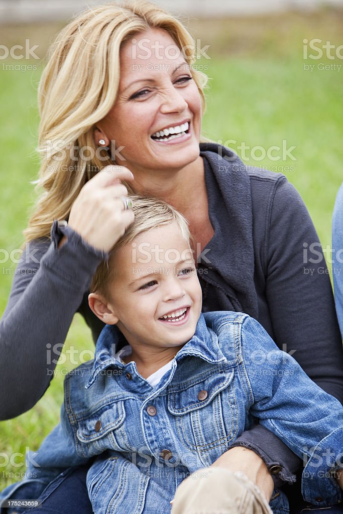 Little boy sitting on mother's lap stock photo