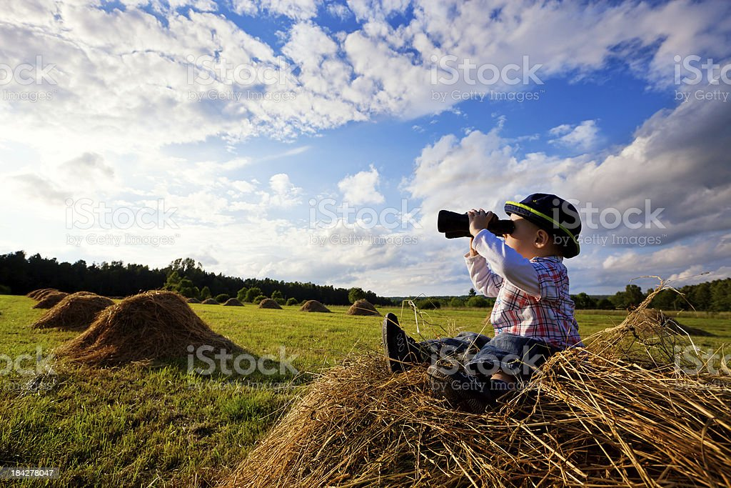 Little boy sitting on mounds of hay stock photo