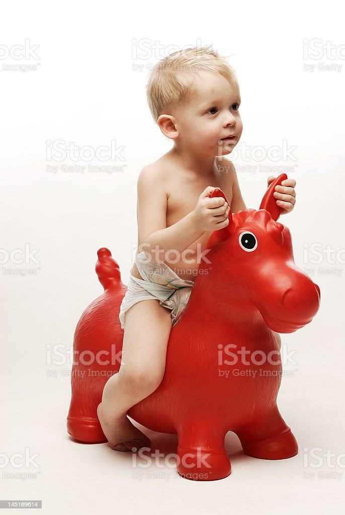 Little boy sitting on red horse holding it by ears royalty-free stock photo