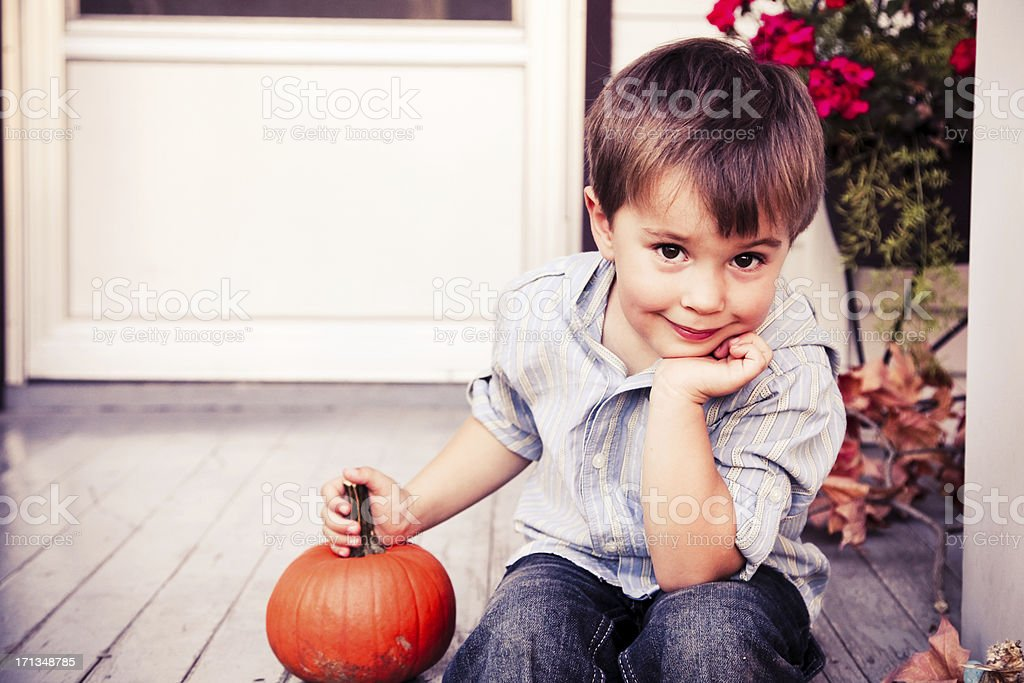 Little Boy Sitting on Steps with Pumpkin- Vintage Toning royalty-free stock photo