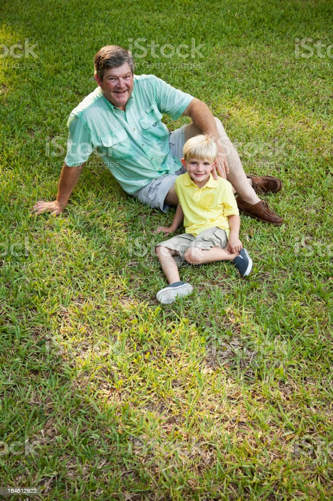 Little boy sitting with grandfather on grass stock photo