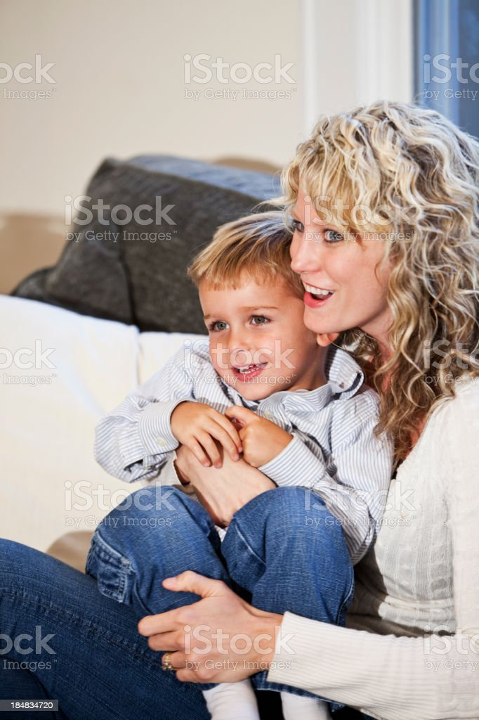 Little boy sitting with mother on couch stock photo