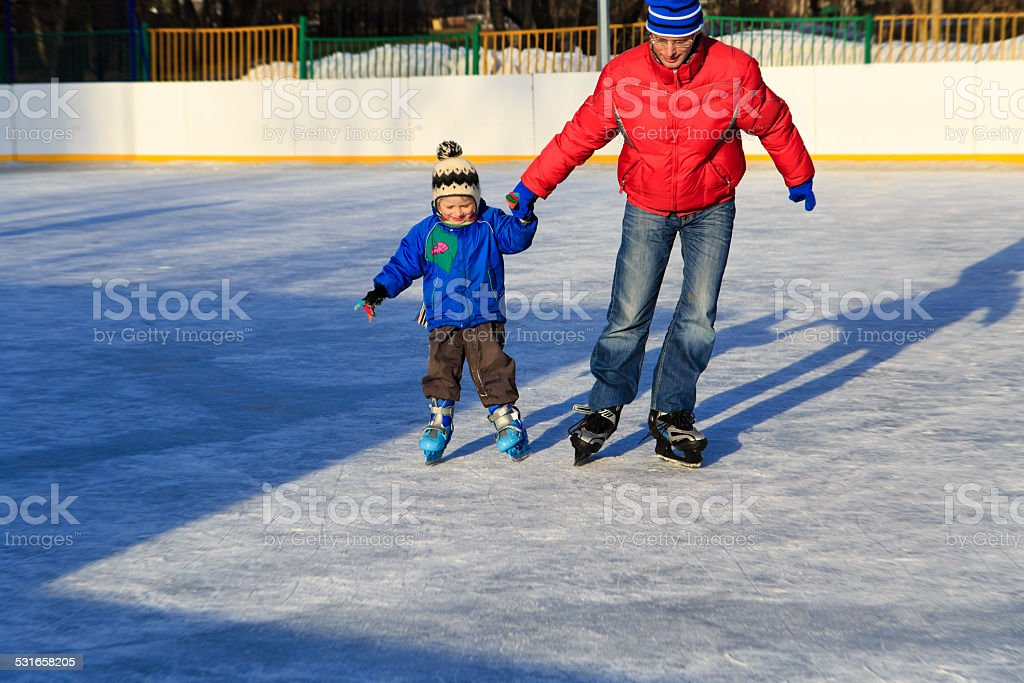 little boy skating with parent stock photo