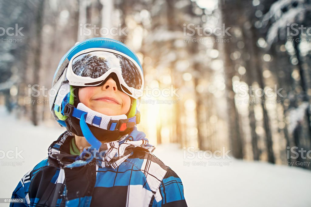 Little boy skiing in snowy forest on sunny winter day stock photo