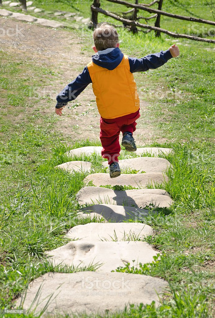 Little boy skipping along a stone footpath stock photo