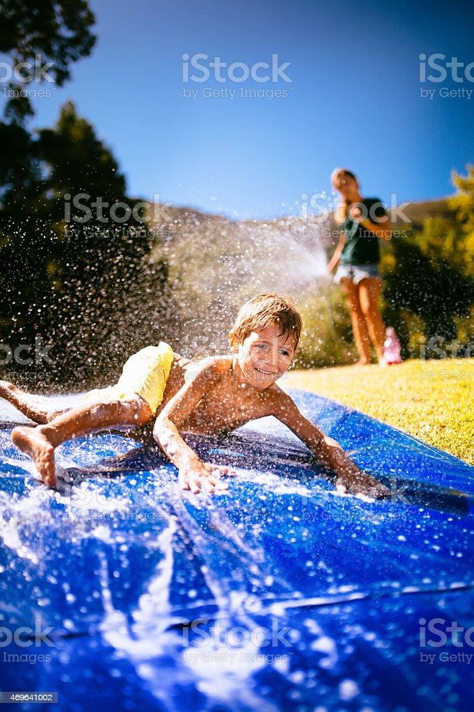 Little boy sliding down slippery water slide outdoors stock photo