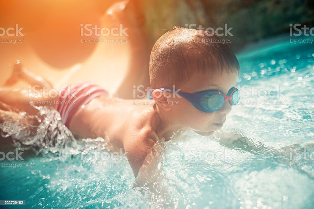 Little boy  sliding into water in water park stock photo