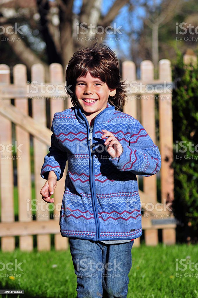 Little boy smiling and running outdoors. stock photo
