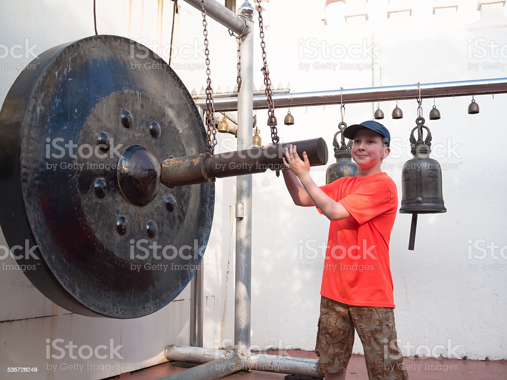 Little boy smiling and strikes the gong stock photo