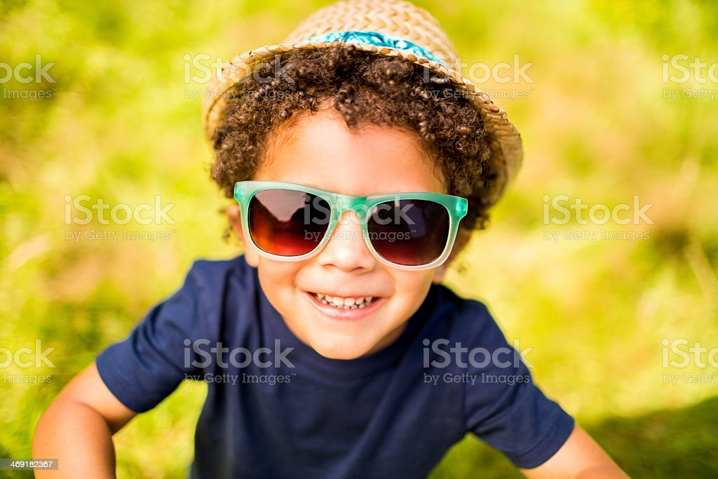 Little boy smiling at camera in park stock photo
