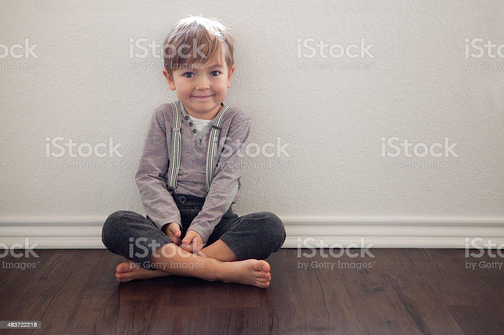 Kleiner Junge lächelnd zeigt nach vorne sitzend auf weiße Wand – Foto