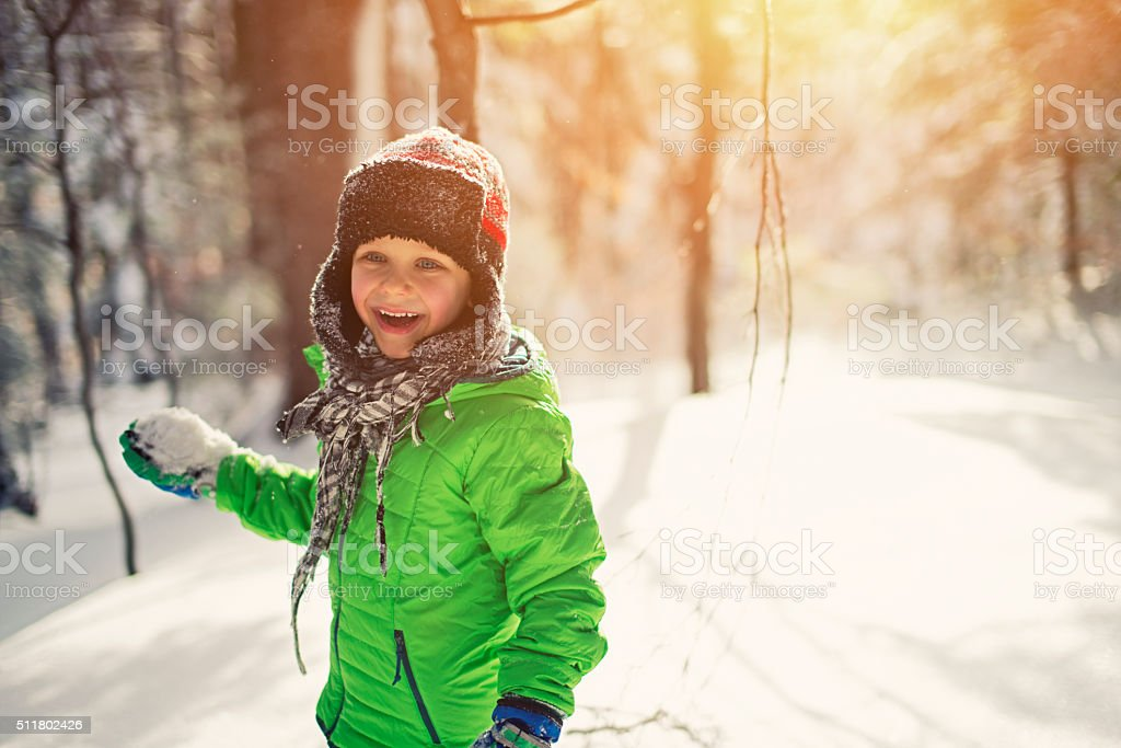 Little boy snowball fight in sunny winter forest stock photo