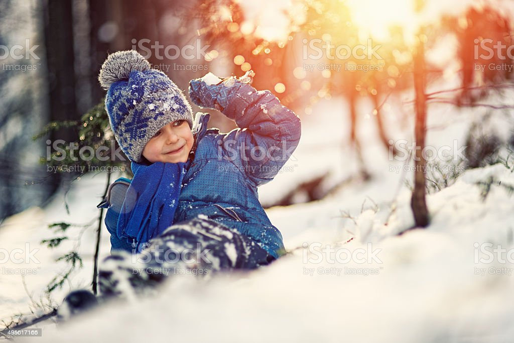 Little boy snowball fight in winter forest stock photo
