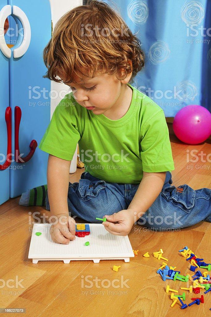 Little boy solving puzzle stock photo